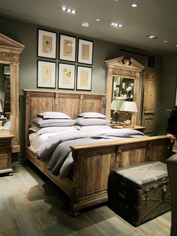 Bedroom in Restoration Hardware with a wood bed frame, chest at the foot of the bed, two large mirrors in antique wood frames