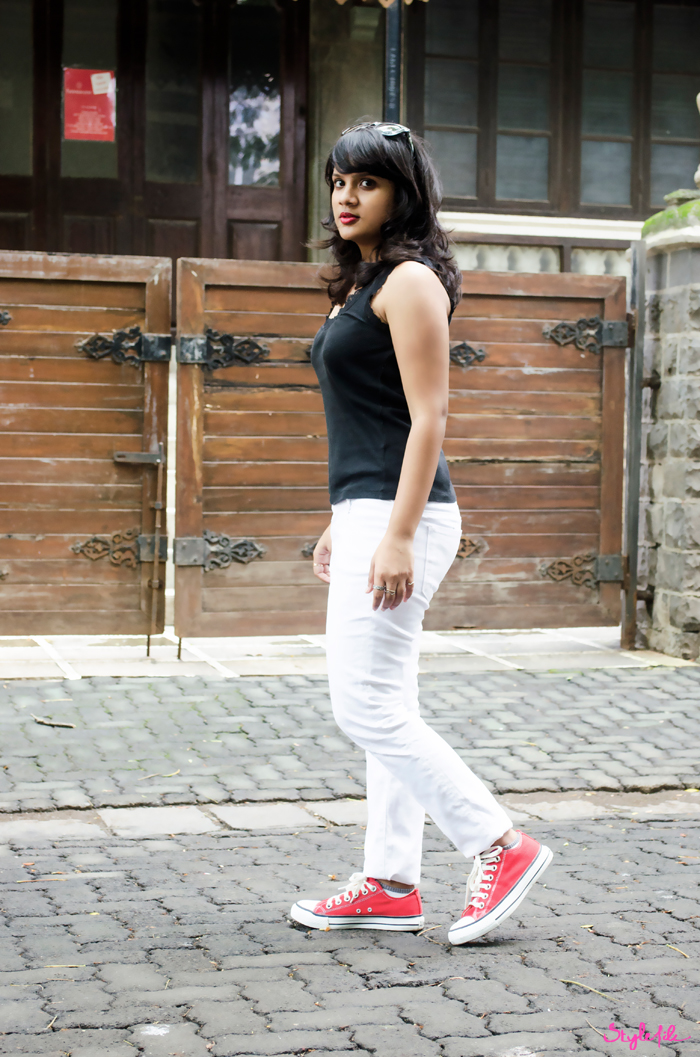 Dayle Pereira of the blog Style File shows her personal style in an outfit with a GAP lace trimmed tank top, Zara ripped denim jeans, NYU cap, Rayban wayfarers, All-star converse sneakers and red lips for a sport chic, athleisure look