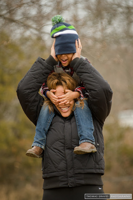 With her son on her shoulders, mom tries to navigate with her eyes covered.
