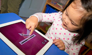 Toddler learning letters on an iPad app.