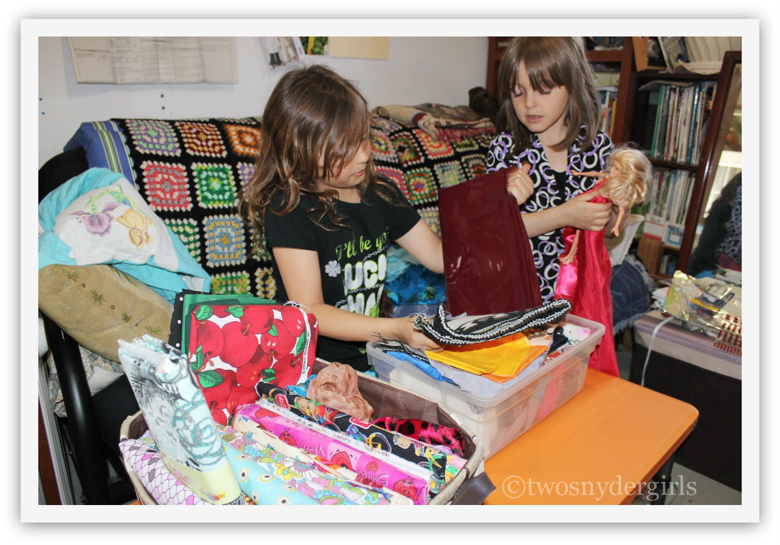 Two girls sorting through cloth for their dolls cloths