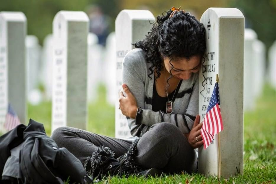 Thania Sayne leans on the headstone of her husband the day before their wedding anniversary on 16 October 2013. - The 63 Most Powerful Photos Ever Taken That Perfectly Capture The Human Experience