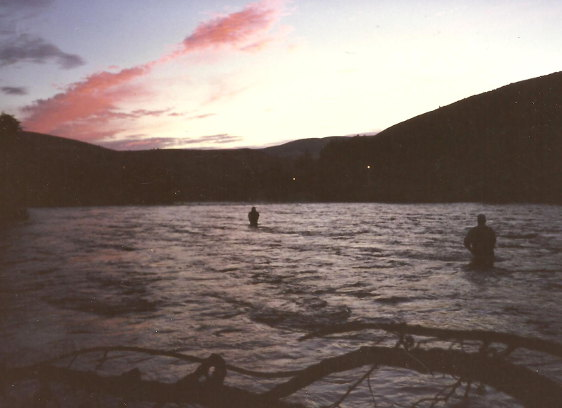 shadows of two men fly fishing at sunset with pink clouds over the darkened rim of hills.