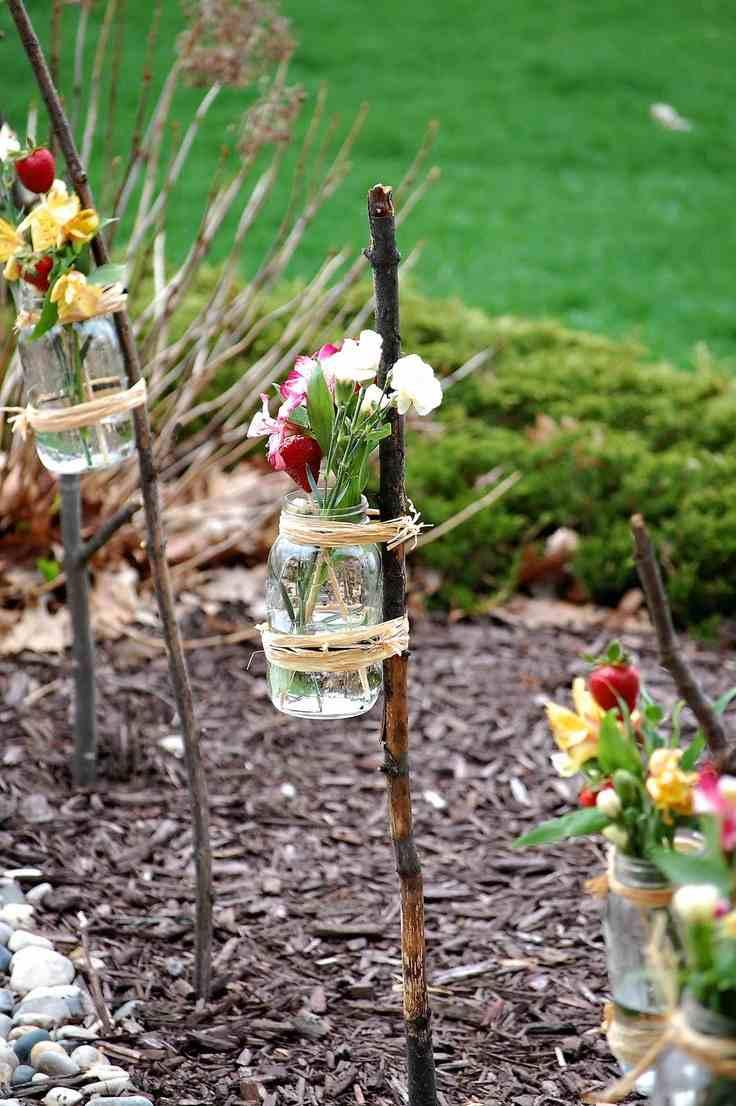 dekoracja z kwiatów w słoikach na kijkach, kwiaty w słoikach na kiju w ogrodzie