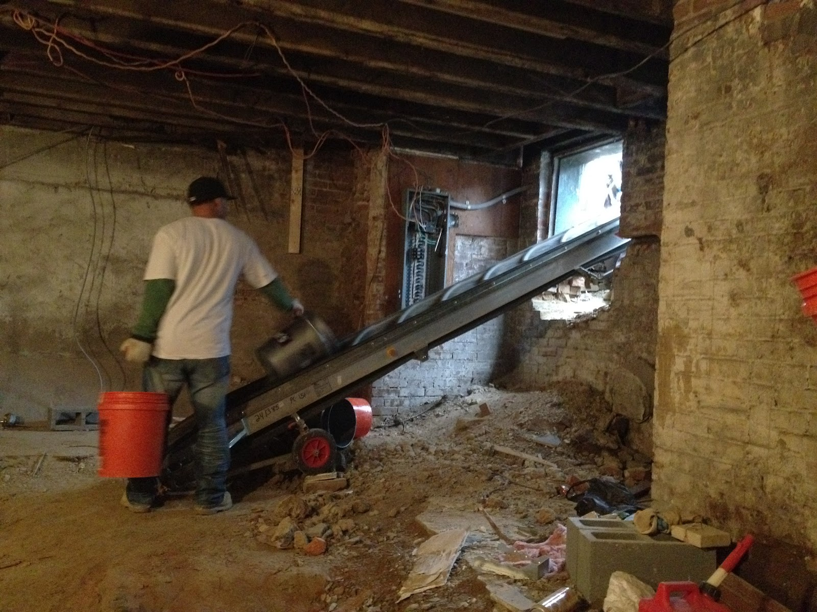 in the basement a crew is using a conveyor belt to remove the dirt so