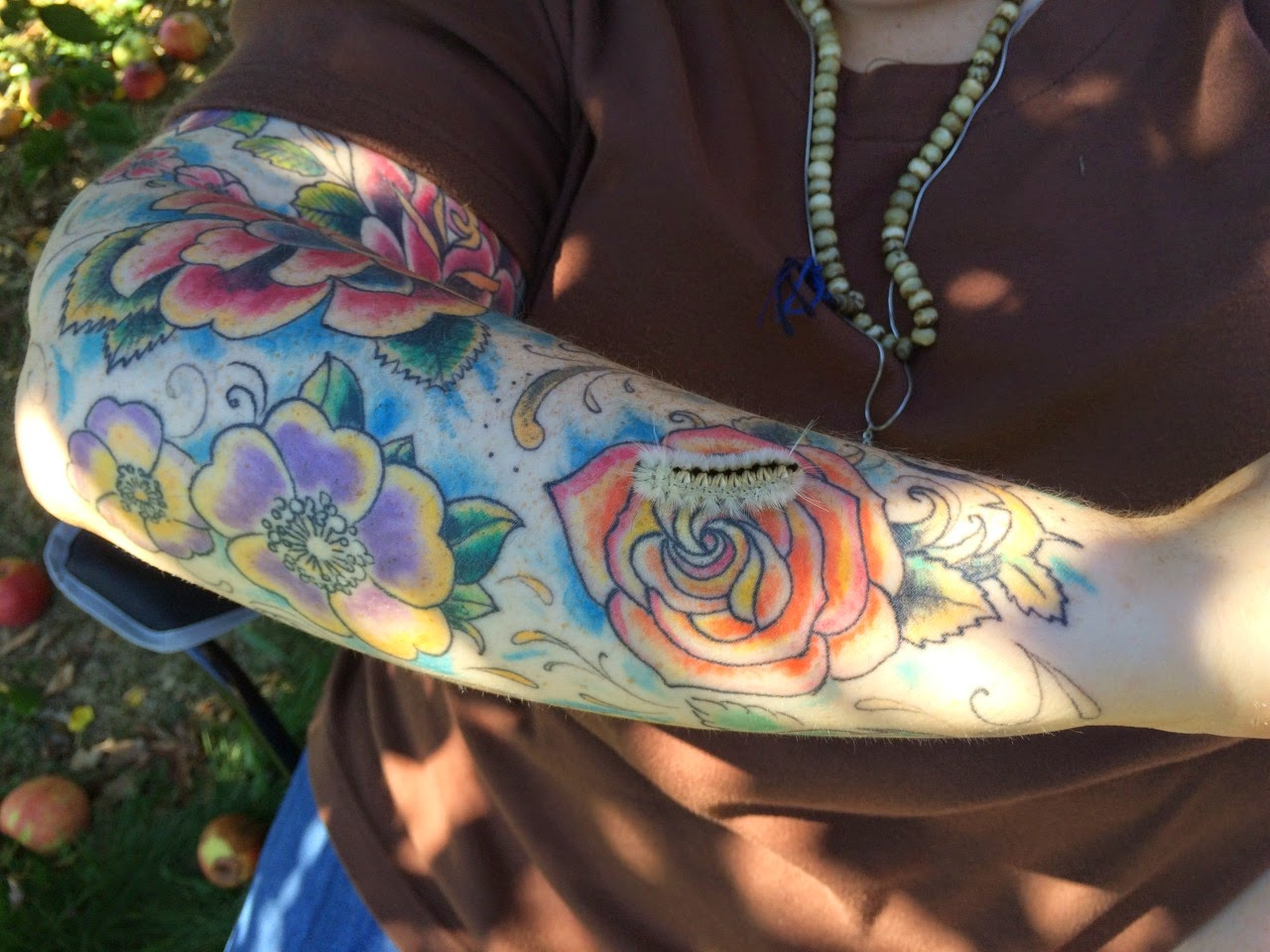 Photograph: An outdoor photo of a tattooed arm covered in different many different roses. On one of these roses there is fuzzy caterpillar.