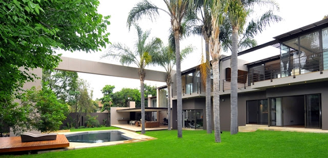 Picture of large modern mansion as seen from the backyard