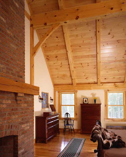 this timber frame bedroom features a soaring cathedral ceiling