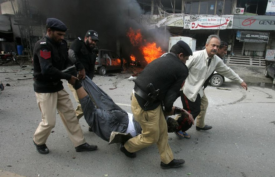 Pakistani police officers and a volunteer rush an injured person to a hospital after a bombing in Lahore, Pakistan, Tuesday, Feb. 17, 2015. An apparent suicide bombing killed many people outside a police complex in eastern Pakistan on Tuesday, officials said, in a rare attack on the relatively peaceful city of Lahore.