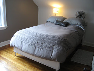 midway picture of bedroom with painted walls, new duvet cover and plain white sloped wall behind headboard