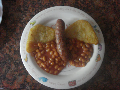 Butterfly made out of Hash browns, sausages and beans