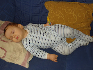 Baby Boy asleep on the sofa holding a spoon