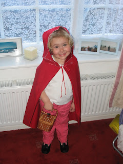 Top Ender wearing a red hood cape with white stitching