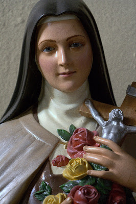 Statue of Saint Therese holding a crucifix and roses.