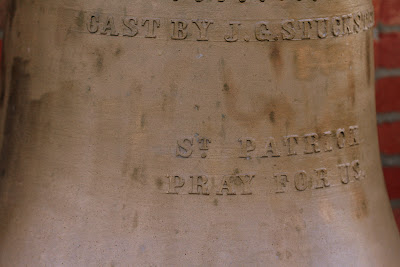 Close up of church bell with inscription St. Patrick pray for us