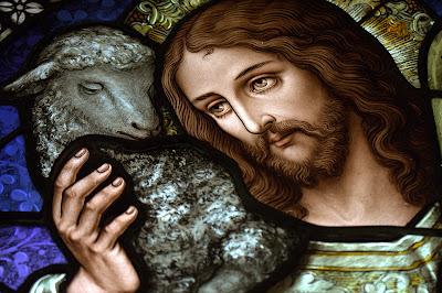 Stained glass window with close-up of Jesus the Good Shepherd with a lamb on his shoulder