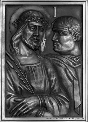 Bronze relief in black in white of Station one of the Stations of the cross.