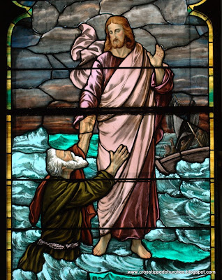 Close up of stained glass window of Jesus walking on water reaching out to Peter.