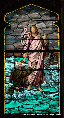 Full stained glass window of Jesus walking on water reaching out to Peter