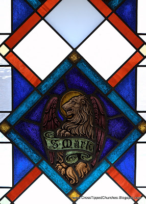 Stained glass window of winged lion with banner reading Saint Mark.