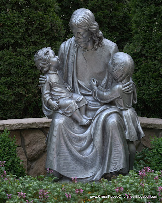 Large gray statue of Jesus holding children.