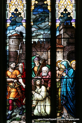 Stained glass widnow of Jesus meeting his mother while carrying the cross.