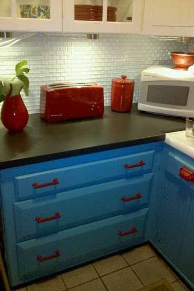 The back splash is clear glass subway tile backed in white for Teal and red kitchen