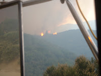 View out drivers window spot fire across ridge