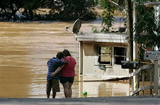 Jennifer Bozeman, 19, and Nabor Torres stand at the edge of Sweetwater Creek after it overflowed its banks and left the mobile home park where they live flooded Tuesday, Sept. 22, 2009, in Austell, Ga. (AP Photo/John Amis)