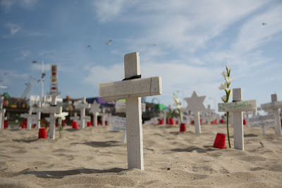 A close up of cross with the California sky and Santa Monica Beach in the background.