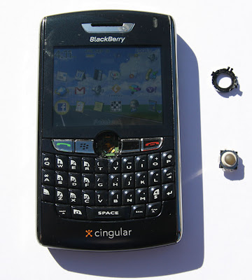 With the silver casing removed, the trackball is removed from the Blackberry.