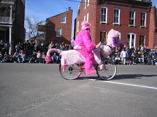 Woman in a pink furry costume riding a bicycle that looks like a pink dog.