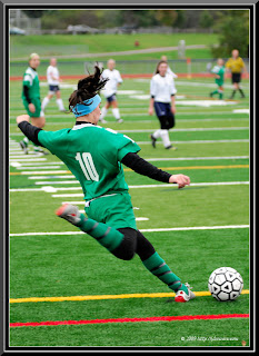 girl in green playing soccer