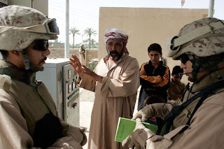 A Marine officer talks through an Iraqi interpreter (L), with the manager of a water pump project near Fallujah. (Joe Raedle/Getty Images)