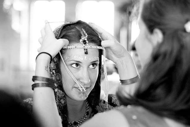 Sister adjusting Indian bride's headpiece