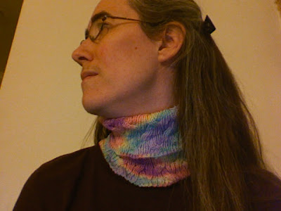 female looking away wearing a hand-knitted pastel cabled cowl