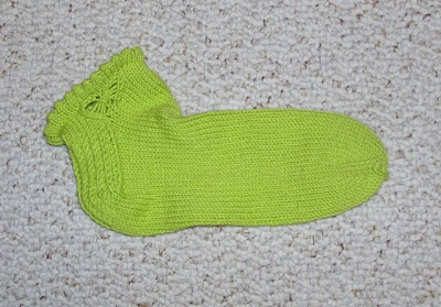 a bright green ankle sock with butterfly embellishment