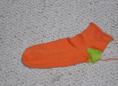 an orange sock with a butterfly embellishment on the ankle and a green heel