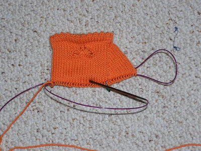 an unfinished orange sock cuff with a butterfly embellishment
