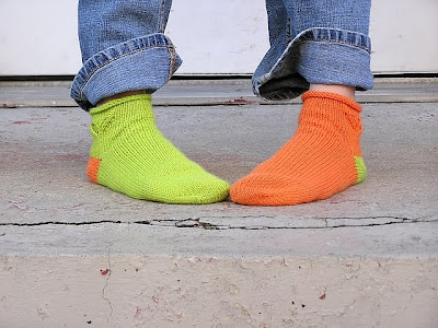green and orange socks, toes together