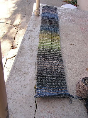 a striped scarf in progress, stretched out to about three feet in length