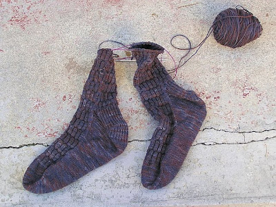 socks knit toe-up, still on the needles, nearly finished, in charcoal grey