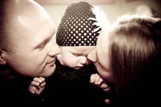 Parents kiss beautiful newborn wearing a beanie