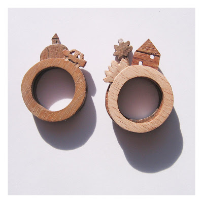 A series of rings intended to be worn together. Each ring depicts a different part of the scene, including a car, a tree and a house.