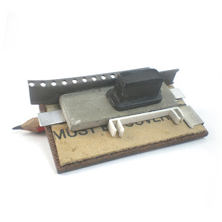 Office assemblage pin, incorporates cardboard, typewriter parts and pencil as part of pin fixture.