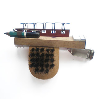 Office inspired brooch which uses an id card clip or pen clip as the fastenings. Brooch also incorporates a clothes brush, pencil, staples and section of a note book.