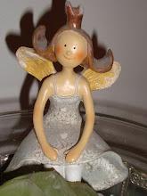 En liten liten ängel på kanten på en silverskål pryder mitt vardagsrum