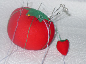 new bright red pin cushion, looking like a tomato with a strawberry attached!