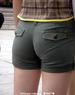 The young woman wearing jeans shorts in the edge of the road