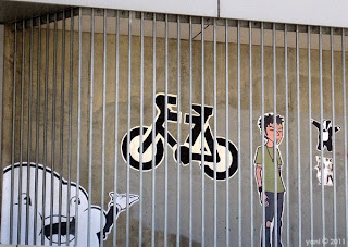 mr sloppy behind bars with trent lane, a bicycle and a dancing badger